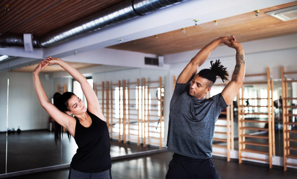 man and woman stretching arms