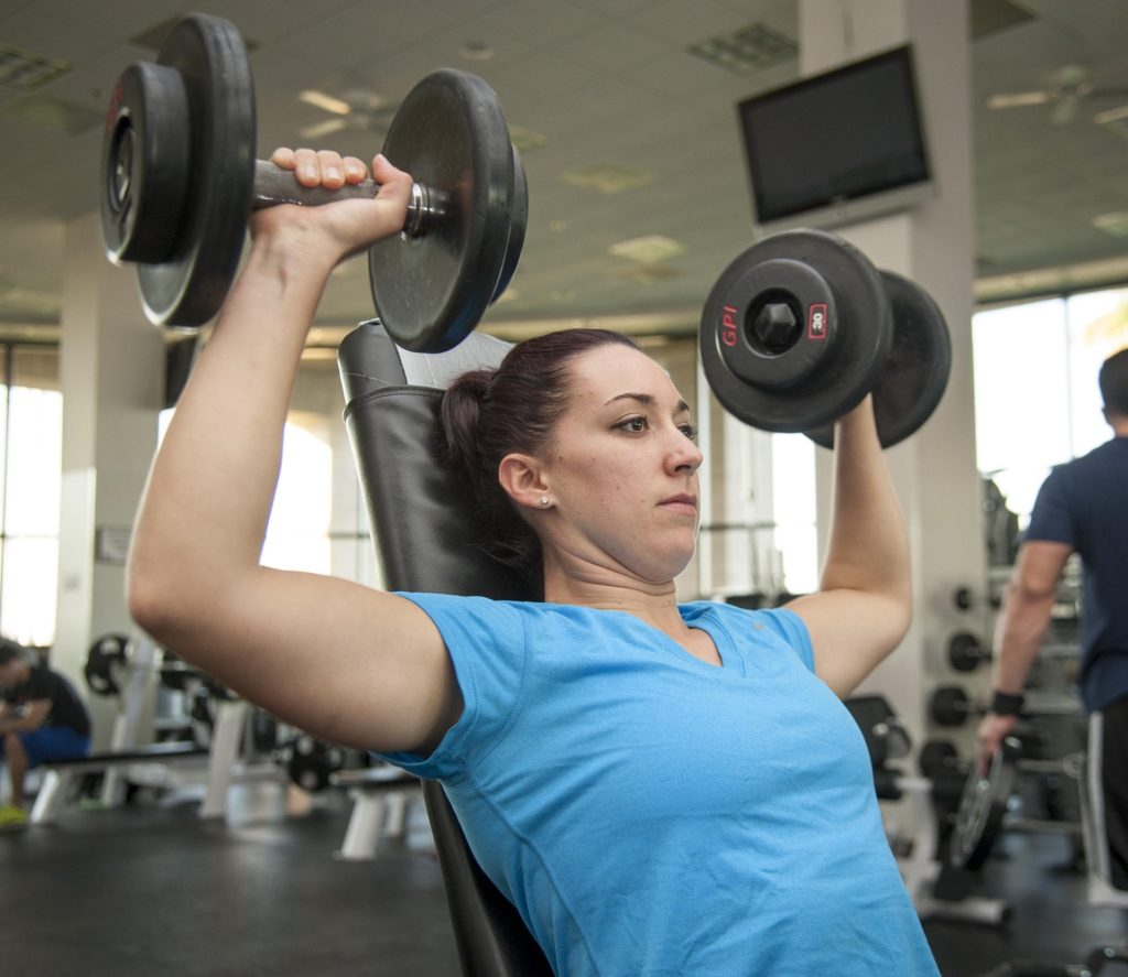 woman in blue shirt lifting weights