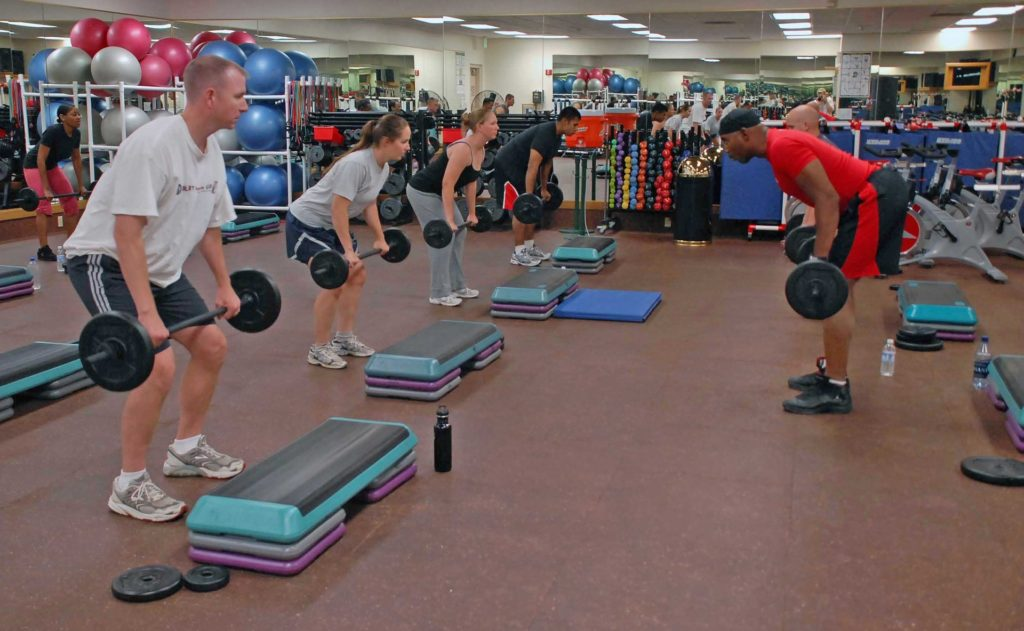 group of people lifting barbell