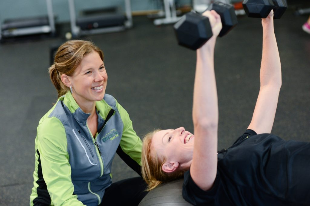 woman being happily assisted by a gym coach
