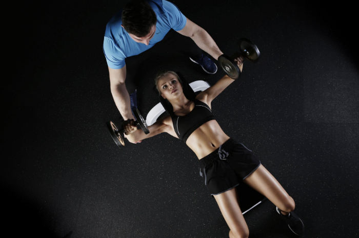 woman lying on bench press holding barbell
